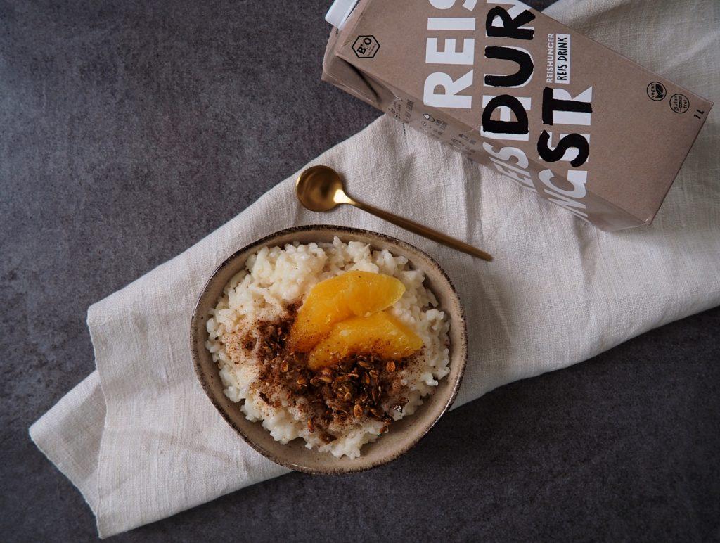 Veganer Milchreis mit der doppelten Portion Reis: ganz easy mit Reisdrink! Dazu frische Orangen, Spicy Choc Gewürz und knuspriges Granola.